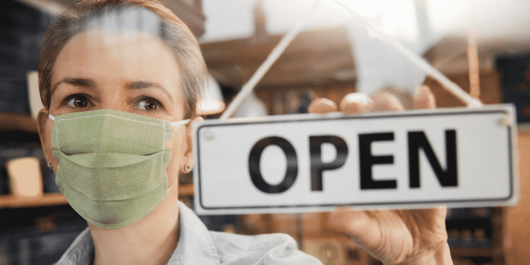 Picture of a business owner wearing a mask holding the OPEN door sign