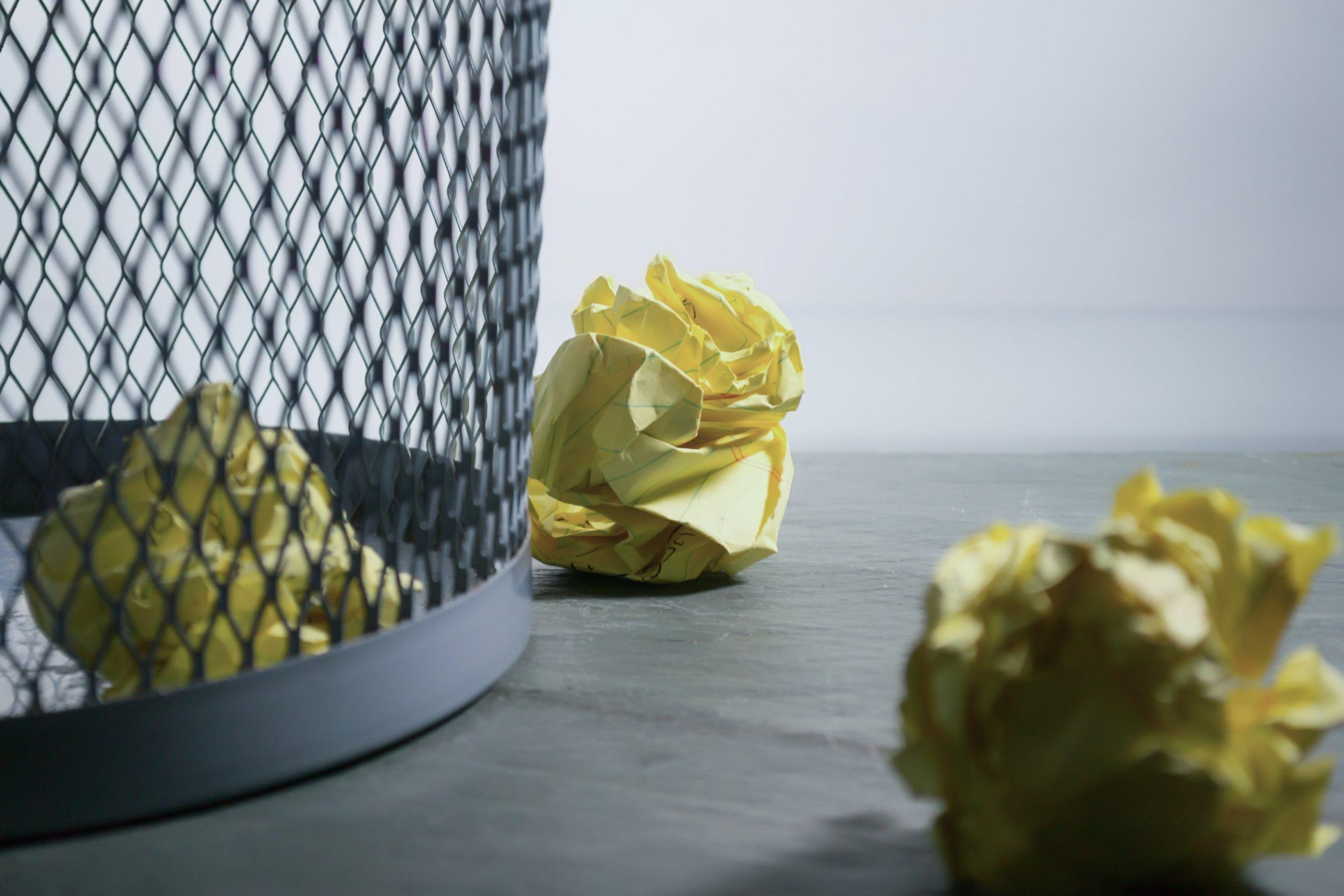 Crumpled paper in and around a bin
