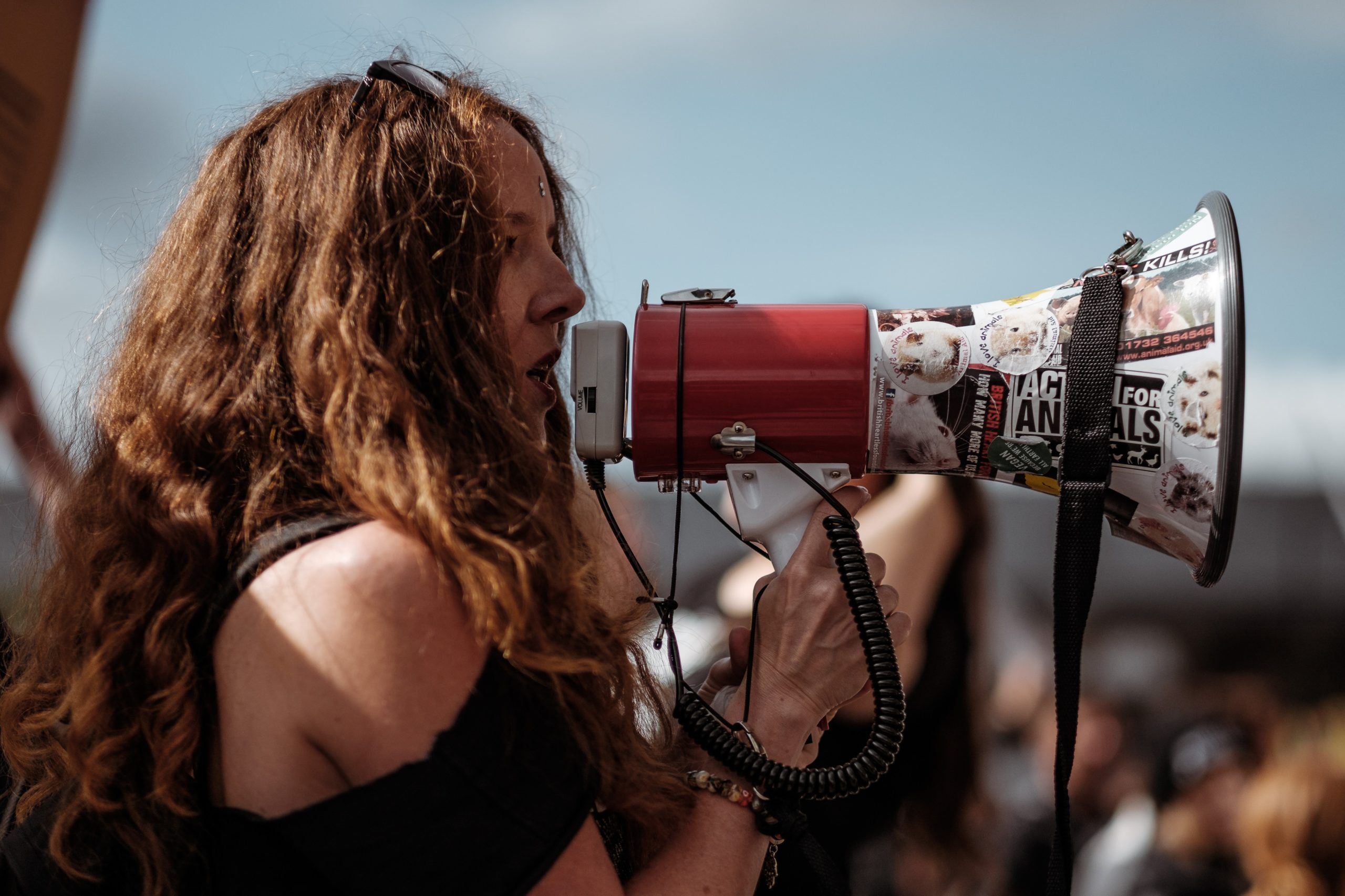 A woman with long brown hair speaking into a megaphone