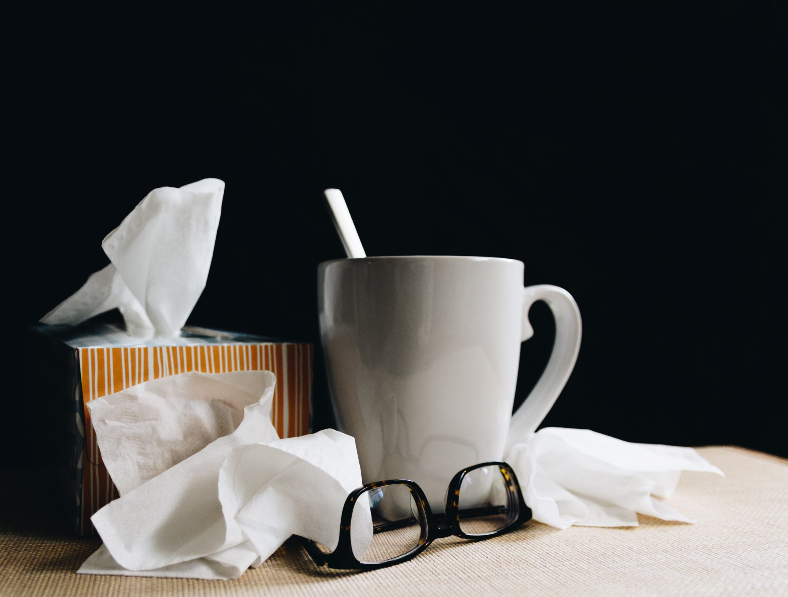 A mug and glasses next to a box of tissues surrounded by used tissues