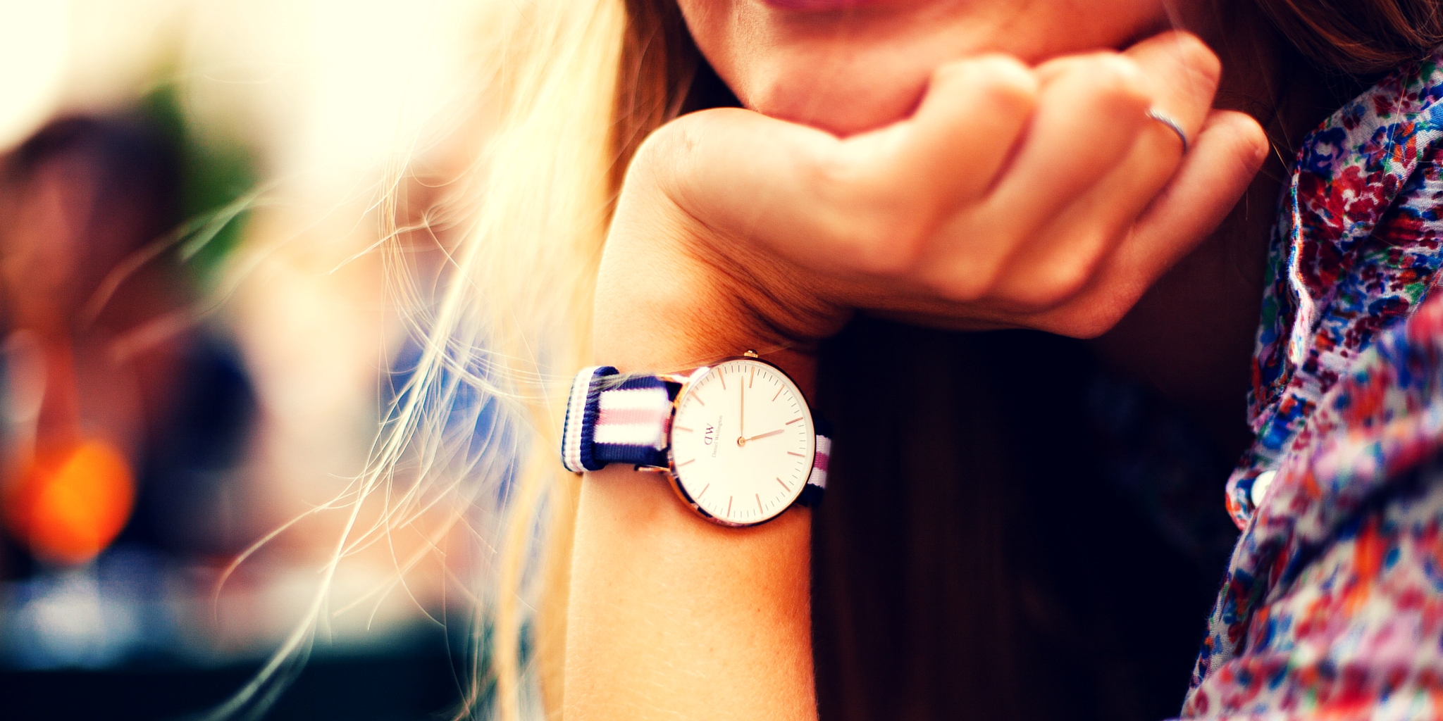Woman resting head on hand, wearing watch, sitting in the sunshine