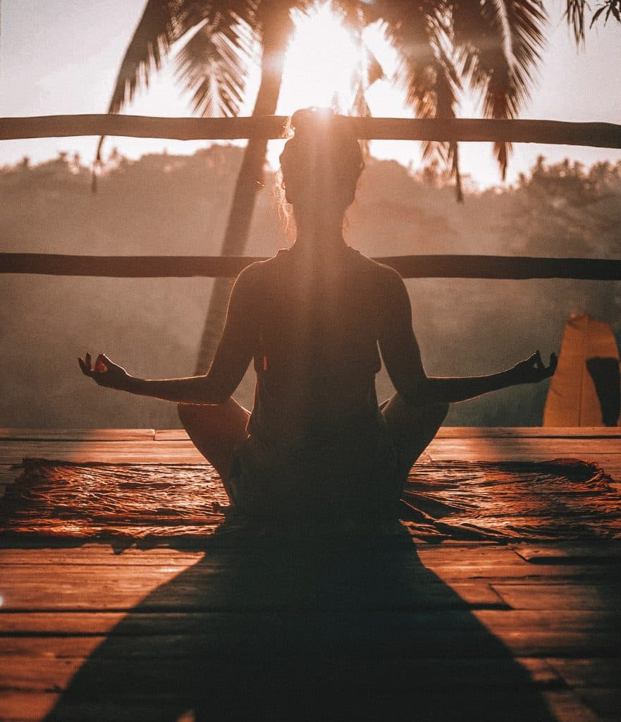 silhouette of a women meditating in the sun