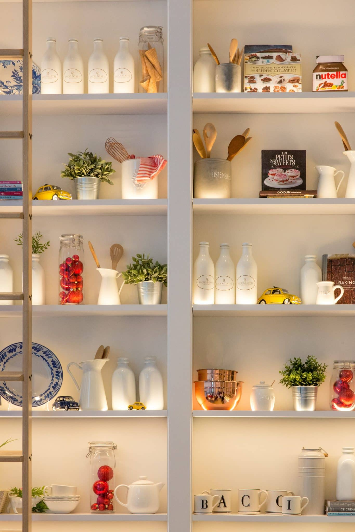 Photograph of a neatly organised pantry. Items in the pantry include glasses, mugs, teapots, jars, plates and condiments.