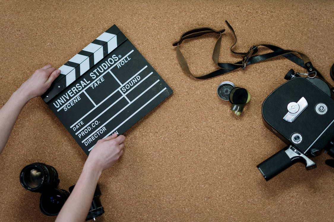 A hand is holding a clapperboard and a camera is beside it.